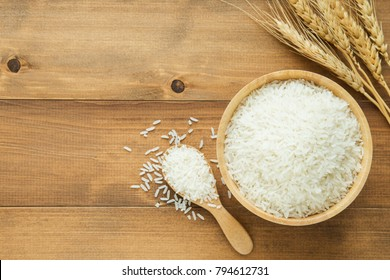 white rice (Thai Jasmine rice) in wooden bowl on wood background