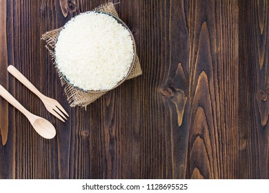 White rice and wooden spoon and fork on wooden table
