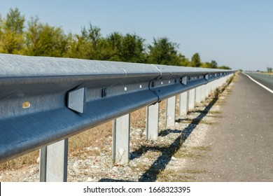 white road reflectors along the road. metal road fencing of barrier type. Road and traffic safety.