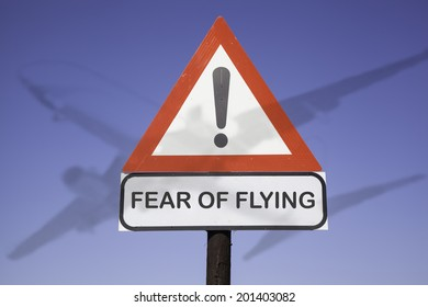 White road warning triangle with black  exclamation point and red frame on  a wooden mast in front of a blue sky. A second rectangular sign warns in english about  fear of flying