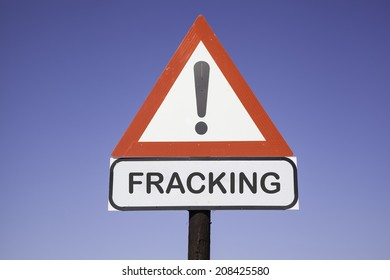 White road warning triangle with black  exclamation point and red frame on  a wooden mast in front of a blue sky. A second rectangular sign warns in english about fracking