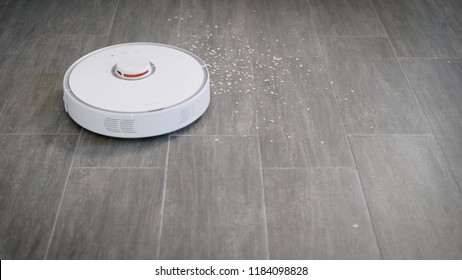 White robot vacuum cleaner device cleaning floor from crumbs at home