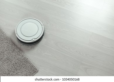 White robot vacuum cleaner on laminate floor cleaning dust in living room interior. Smart electronic housekeeping technology, top view with copy space