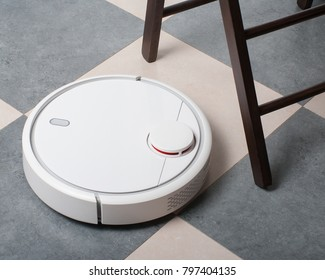 White robot vacuum cleaner on floor made of laminate beside the chair in kitchen. Modern home technology lifestyle