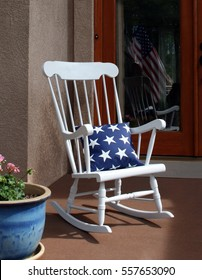 White rocking chair on 4th of July front porch with American flag reflected in background