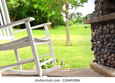 White rocking chair on patio, open green field with tree. Relaxing scene in home garden, older home.