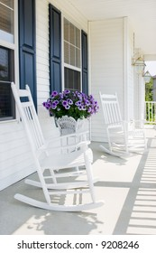 white rocking chairs with purple petunias on a suburban covered porch