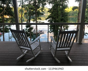 White rocking chairs with view of a lake and dock