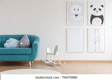 White rocking horse for children standing next to turquoise couch in interior with four posters