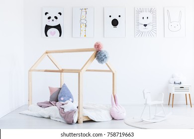 White rocking horse in child's bedroom with DIY bed and white cabinet against wall with posters
