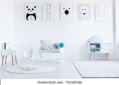White rocking horse on carpet in baby's bedroom with cupboard and white cradle with pompons