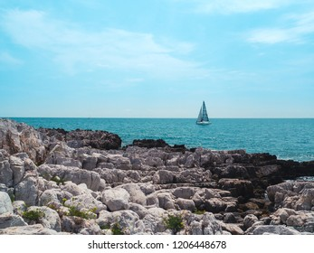 White rocks and mediterranean sea with sailing boat and blue sky