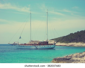White rocky beach, clear blue sea and a moored boat, on a sunny day. Image filtered in faded, retro, Instagram style with extremely soft focus; nostalgic, vintage concept of summer holidays.