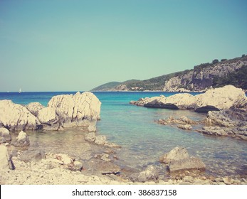 White rocky beach and clear blue sea on a sunny summer day. Image filtered in faded, retro, Instagram style with extremely soft focus; nostalgic, vintage concept of summer travel and holidays.
