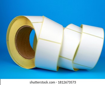 White roll of labels for thermal perforation on a blue background. Babina of self-adhesive stickers. Self-adhesive white label roller for printing or manufacturing