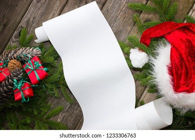 A white roll of paper between fir branches on a wooden table