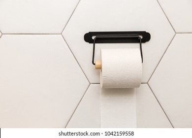 A white roll of soft toilet paper neatly hanging on a modern chrome holder on a light bathroom wall.