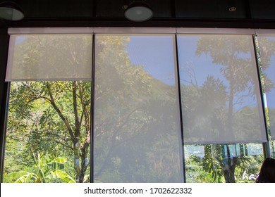 white roller blinds or curtains at the glass window