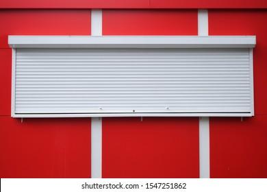 赤いキオスクに白いローラーシャッターが付いています。街頭小売、店舗、市場。現代の安全と安全。