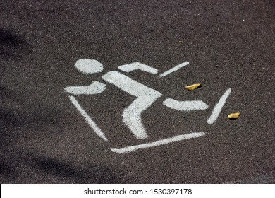 White rollerskiing sign on black asphalt on the street