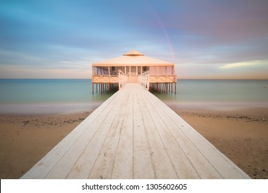 White Romantic Pier on water with Real Rainbow, long exposure, sunset time