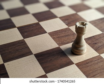 White Rook chess piece isolated on a wooden chess board. Strategic placement and play. Rich brown and white checkered board. Mind using boarding games with tactics and skills.