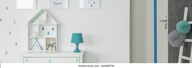 White room with blue lamp and doll house on commode