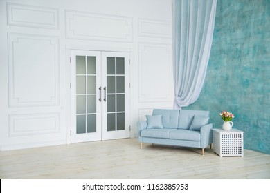 White room is a blue sofa, a pedestal with flowers in a vase.