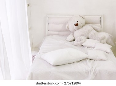 white room corner with bed teddy bear and window with white curtain
