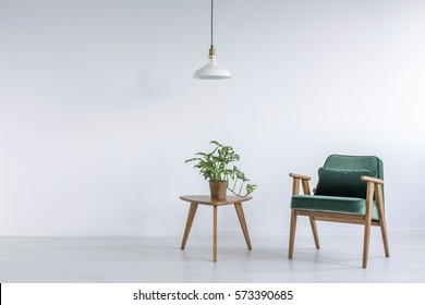 White room with green armchair, small table and plant