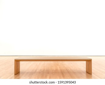 White room in a museum with a bench.