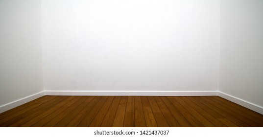 White room. Three walls of a white room with wood flooring and white trims.