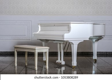 White room with white wooden grand piano and chair standing close, classic modern music room