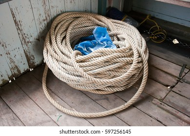 White rope at the corner of a boat waiting to be used to fasten the boat when it will dock.
