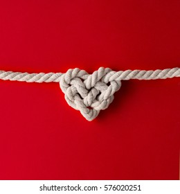 White rope in heart shape knot on red background. Love concept. Flat lay.