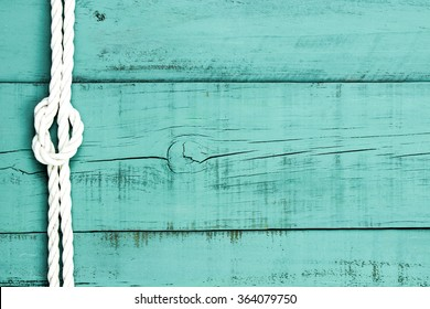 White rope with knot on blank antique mint green rustic wood background; sign with painted green copy space