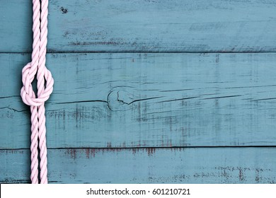 White rope with knot on blank antique gray blue rustic wood background; sign with painted blue copy space