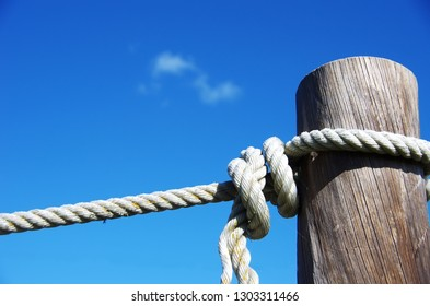 White rope tied with knot to wooden pole