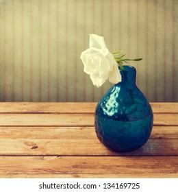 White rose in blue vase over retro background