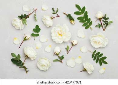 White rose flowers and green leaves on light gray background from above, beautiful floral pattern, vintage color, flat lay styling