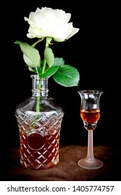 White rose in full bloom standing in a glass decanter of brandy. Small slim pink stemmed glass with brandy in next to decanter. A still life composition on a brown surface with a black background.