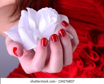 White rose in hand with red nail