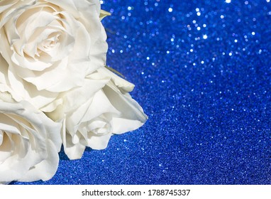 White rose out of focus on a beautiful shining blue background, mock up for greeting cards, wedding, birthday and other holidays, selective focus