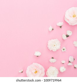 White roses arrangement on pink background. Flat lay, top view.  Pastel background.