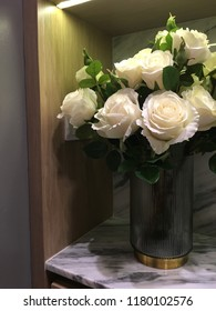 White roses in a beautiful  vase on a marble table.