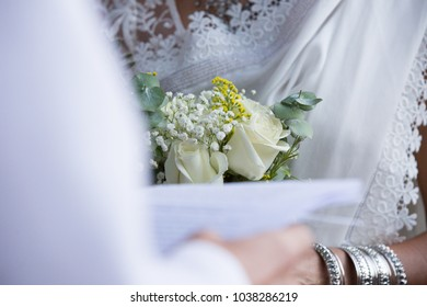 White roses bouquet between groom and bride. Grooms wedding vows. Wedding concept.  White bridal flower bouquet. Until death do us part.