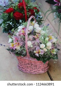 White roses bouquet inside pink wicker basket