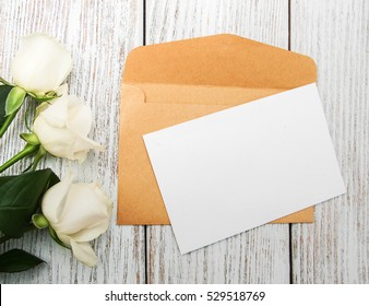 White roses with envelope on a old white wooden table