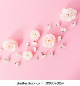 White roses flowers arrangement on pink background. Flat lay, top view. Spring pastel background.