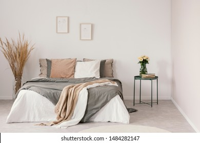 White roses in glass vase and books on metal nightstand next to king size bed with cozy bedding